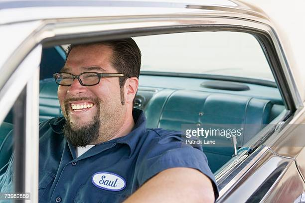 Laughing man driving an older car