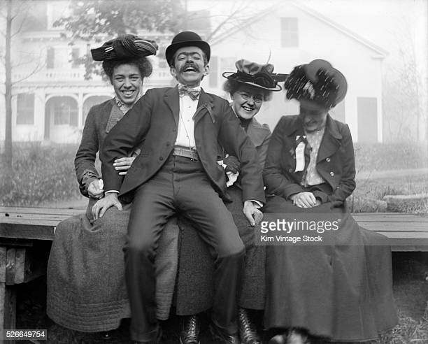 A laughing man engages with three turn of the century women for a carefree protrait