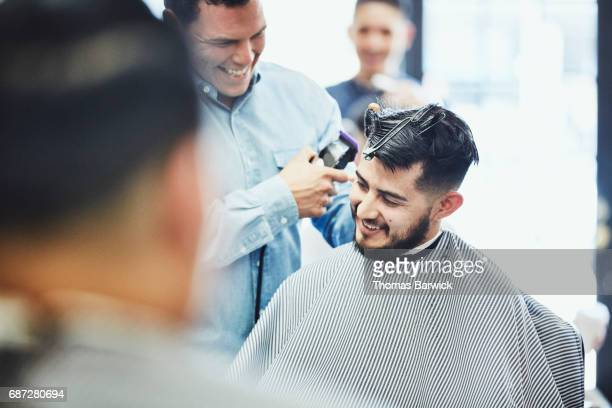 Laughing man in discussion with smiling barber while having hair cut in barber shop