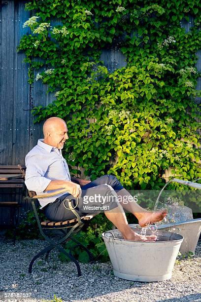 Laughing man taking footbath in a garden