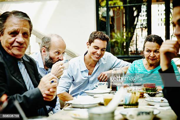 Laughing man with family at dinner party