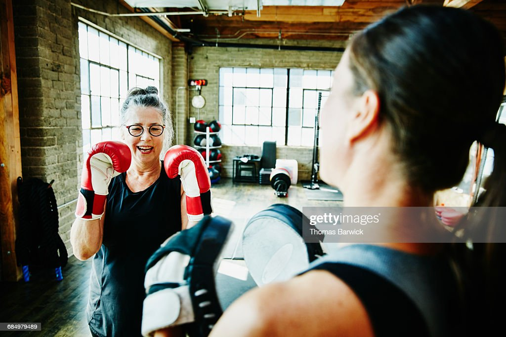 Laughing mature woman boxing with coach in gym : Stock Photo
