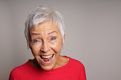 happy mature senior woman with short white hair laughing