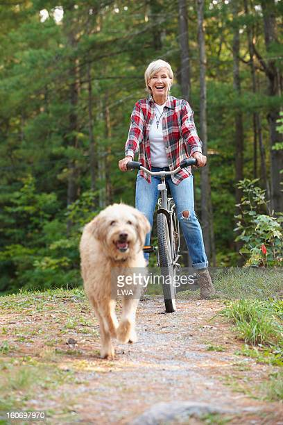 Laughing mature woman watching dog run