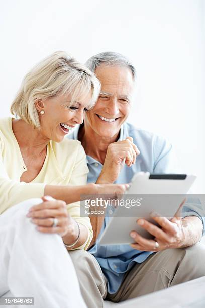 Lachen Ältere Frau mit einem Mann zeigt in touchpad-Bildschirm
