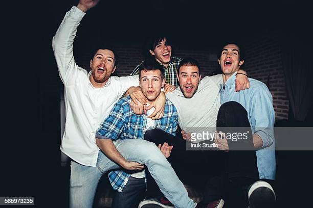 Laughing men playing at party at night