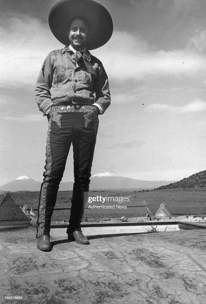 A laughing Mexican 'charro' can be seen with volcanoes Popocatepetl Iztaccihuatl off in the distance 1955