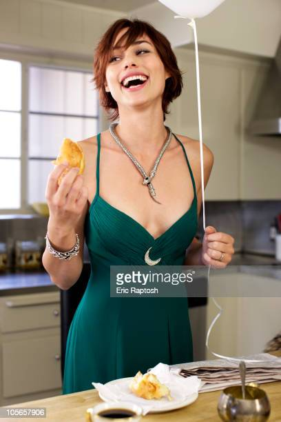 Laughing mixed race woman in kitchen at party