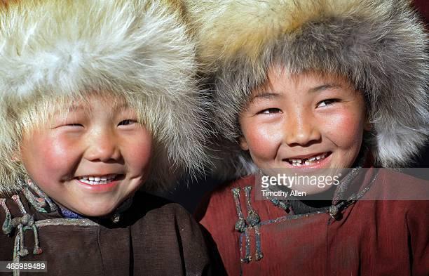 Laughing Mongolian nomadic boys wearing fur hats