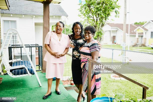 Laughing mother and adult daughters standing on front porch of home before church