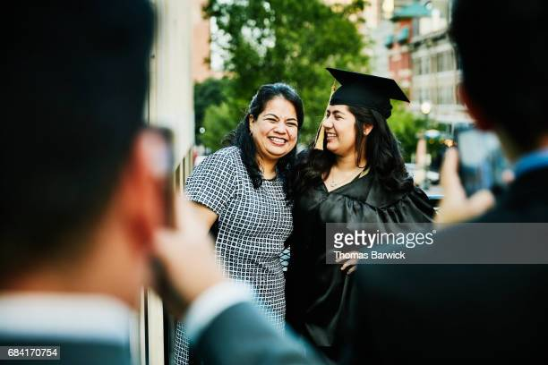 Laughing mother and daughter posing for graduation photos during dinner on restaurant deck
