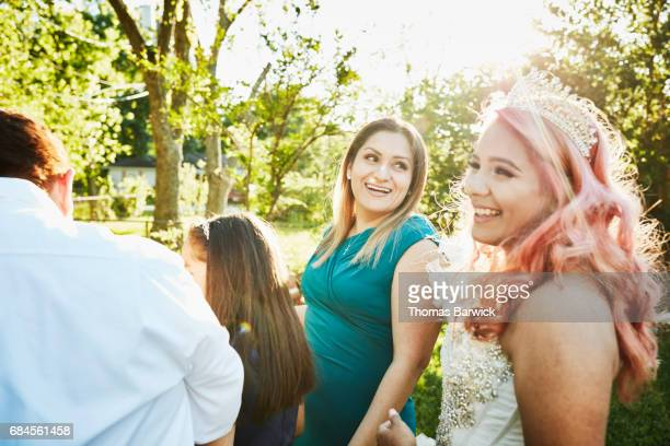 Laughing mother standing with family and daughter in backyard before quinceanera