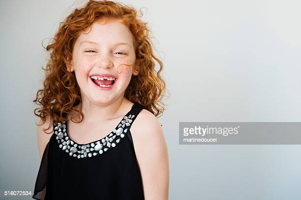 Laughing redhead little girl with freckles and missing tooth.