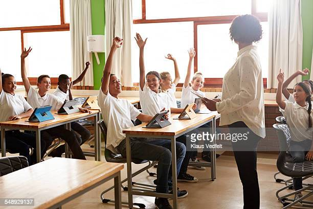 Laughing school class with raised hands