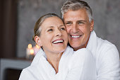 Smiling husband embracing cheerful wife from behind at spa. Laughing mature couple enjoying a romantic hug at wellness center after massage. Senior man and woman in white in bathrobe relaxing at spa.