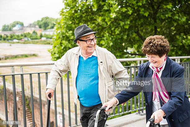 Laughing senior couple with walking stick and wheeled walker