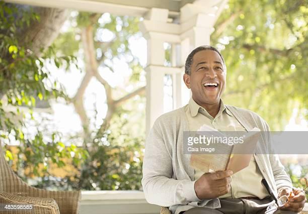Laughing senior man reading book on porch