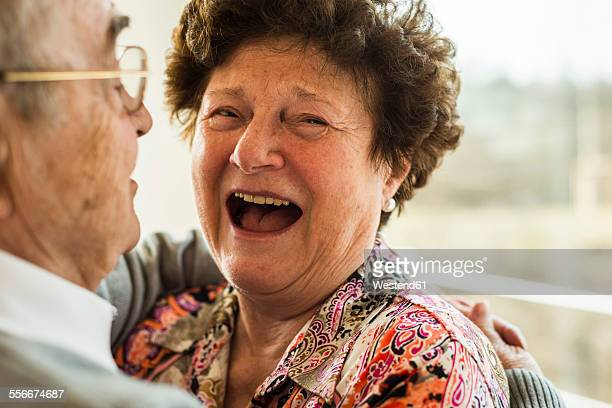 Laughing senior woman in the arms of her husband