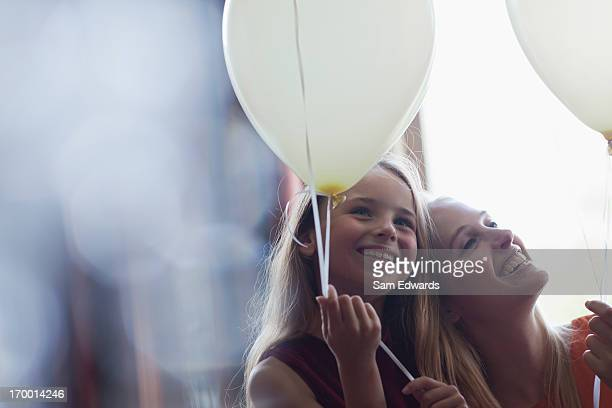 Laughing sisters with balloons
