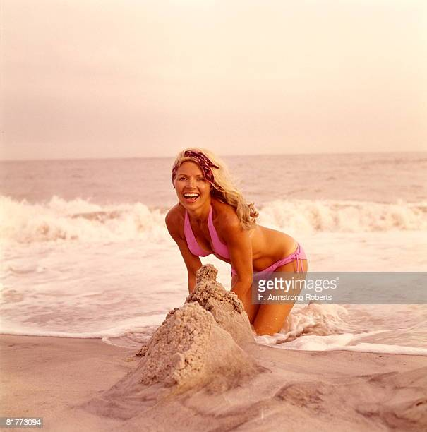 Laughing Smiling Blonde Blond Woman Kneeling Playing Sand Surf Wearing Lavender Bikini Swim Wear Bathing Suit.