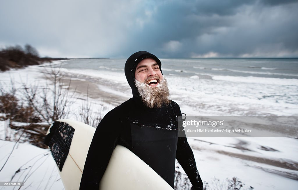 Laughing surfer with beard, beside Lake Ontario in winter