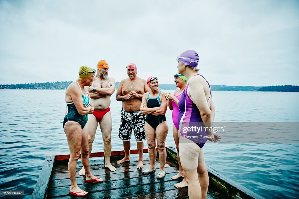 Laughing swimmers on dock before morning swim