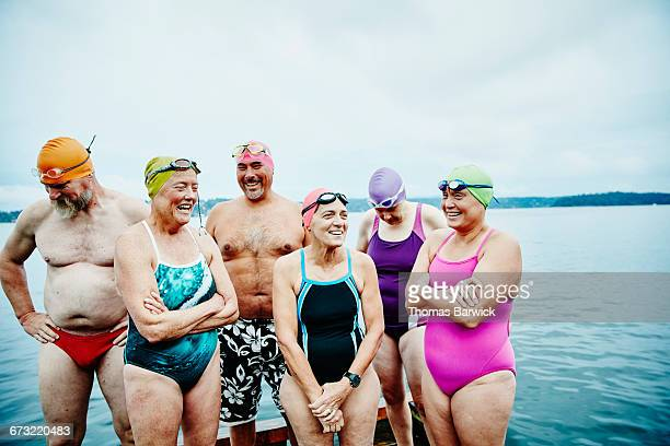 Laughing swimmers standing on dock before swim