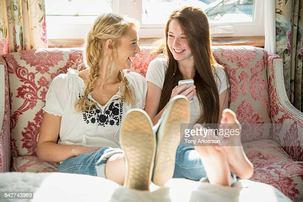 Laughing teen girls at home with phone