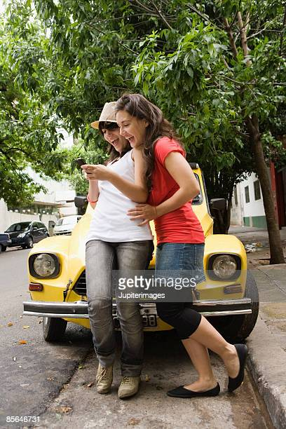 Laughing teenage girl and woman with cell phone