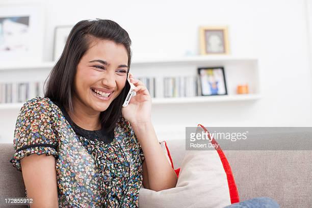 Laughing teenage girl talking cell phone