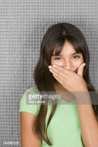 Laughing teenage girl with hands over mouth