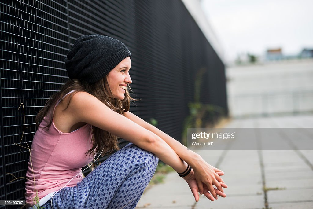 Laughing teenage girl with wool cap crouching in front of a black facade