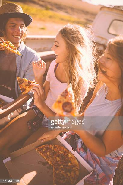 Laughing teens sharing pizza outside on a summer day