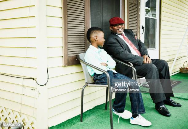 Laughing uncle in discussion with nephew on front porch of home