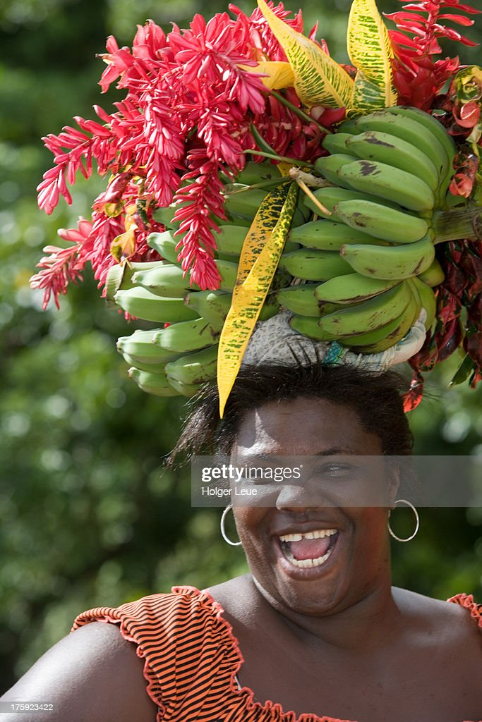 Laughing woman carries fruit on head : Stock Photo
