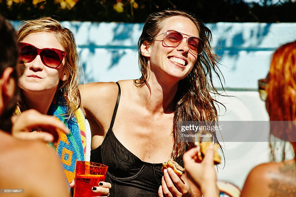 Laughing woman eating with friends during party : Stock Photo