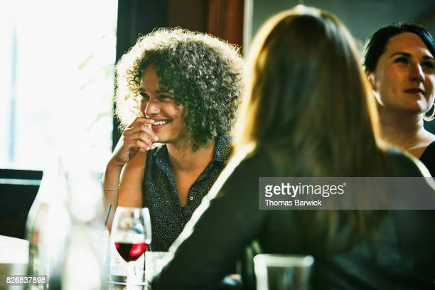 Laughing woman hanging out with female friends in bar