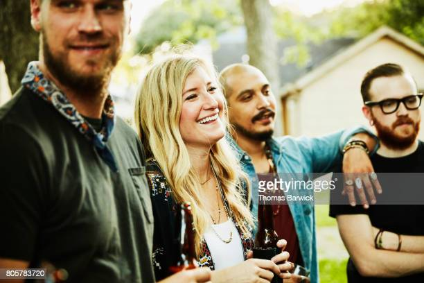 Laughing woman hanging out with friends in backyard on summer evening