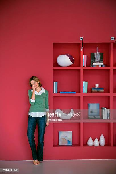 Laughing woman leaning against red wall