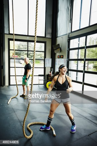 Laughing woman next to climbing rope in gym : Stock Photo