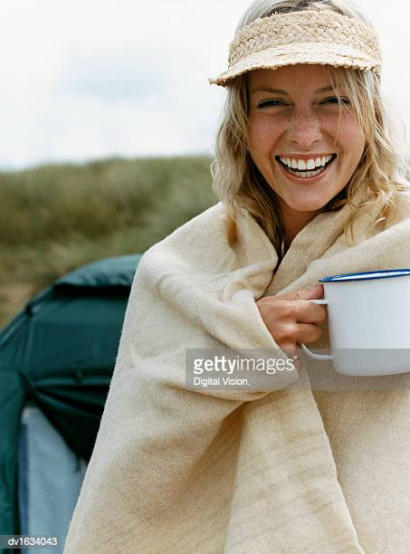 Laughing Woman Outdoors Wrapped in a Blanket and Holding a Mug