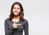 Young beautiful woman pointing at copy space