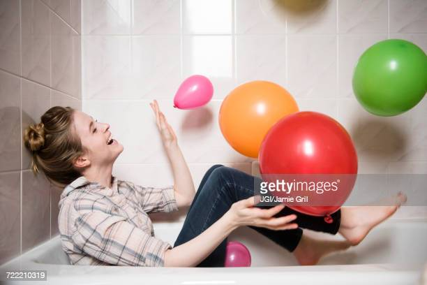 Laughing woman sitting in bathtub playing with multicolor balloons