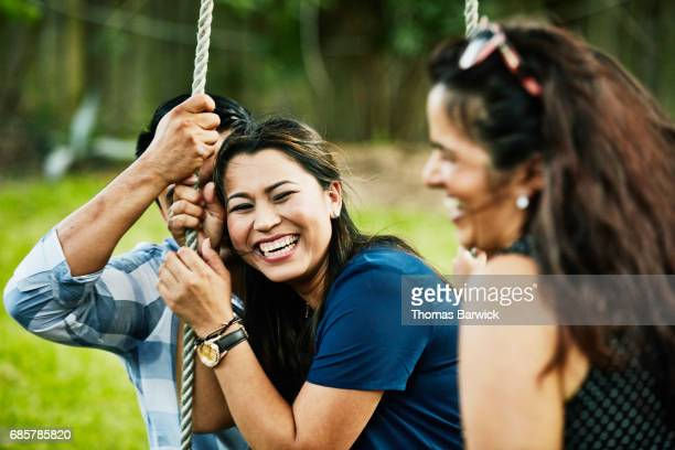 Laughing woman sitting on husbands lap on swing during backyard party