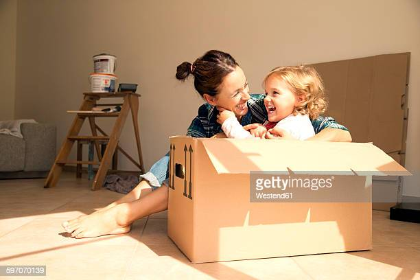 Laughing woman with daughter sitting in cardboard box