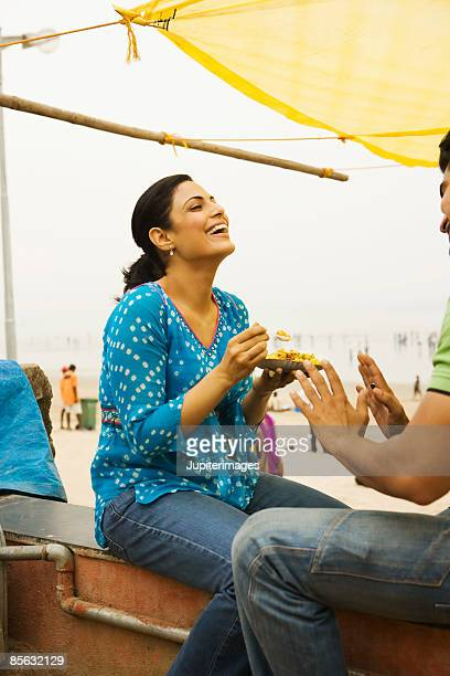 Laughing woman with plate of bhelpuri