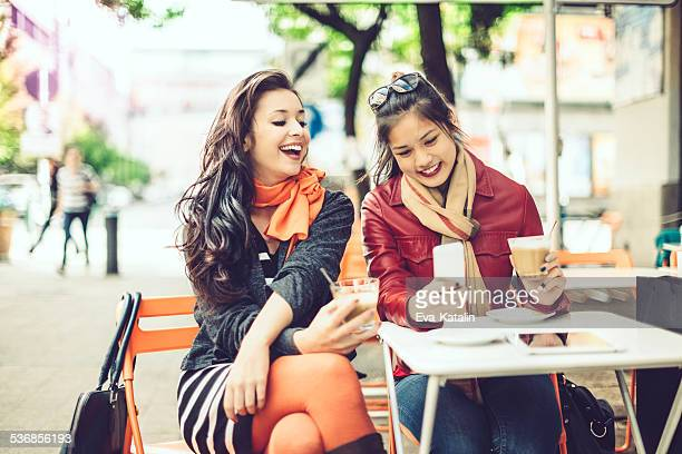 Laughing women are texting in a cafe