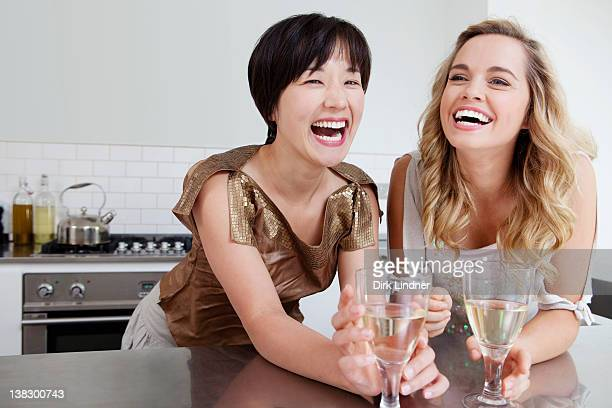 Laughing women drinking wine together