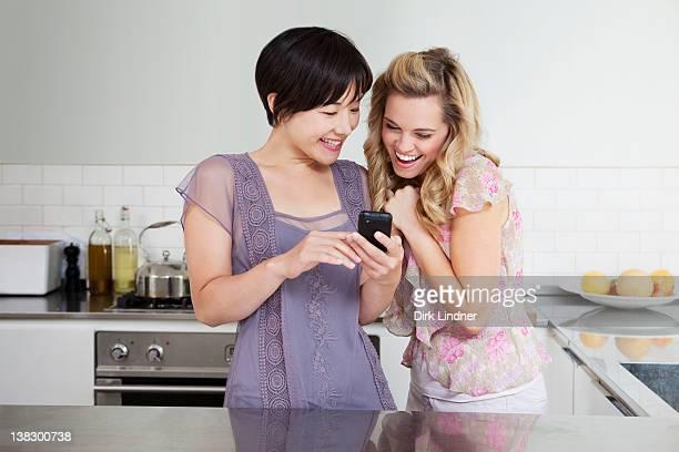 笑う女性の携帯電話を使用して