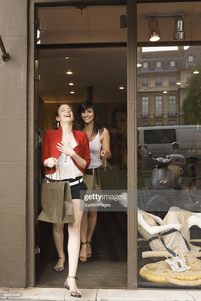 Laughing women walking out of clothing store : Stock Photo